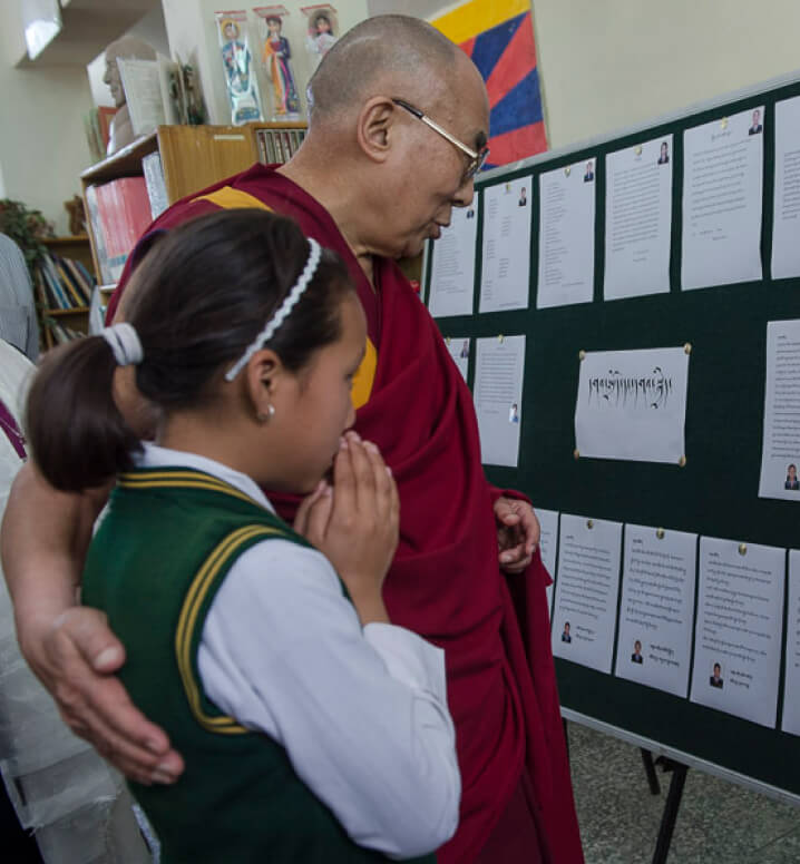 HHDL and a child reading off of a board