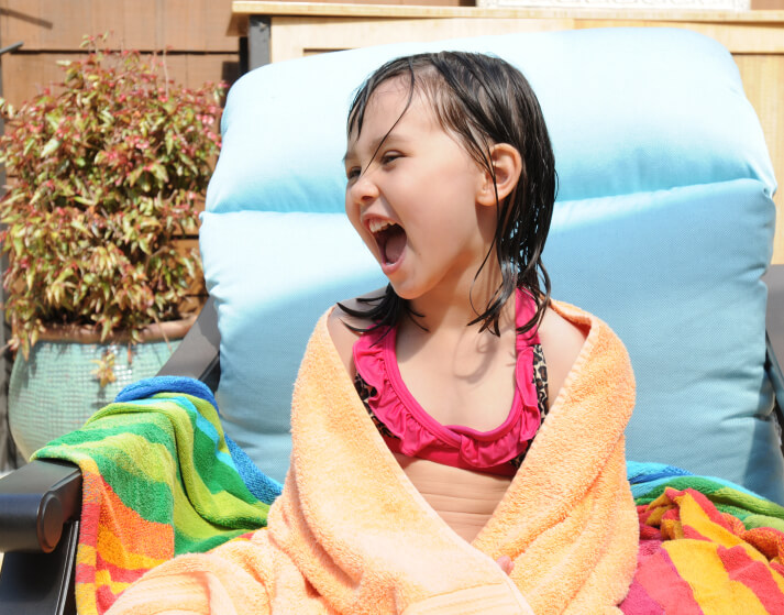 little girl having a good time at the pool lounging
